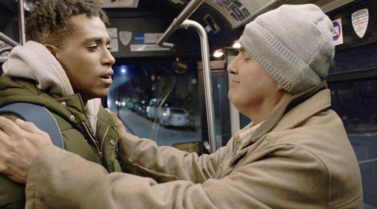 Cena do curta Feeling Through. Nela, vemos Artie e Terek dentro de um ônibus. Artie, um homem branco, careca, cego e surdo, segura Terek, jovem negro, pelos braços, num sinal de agradecimento. Artie está de olhos fechados, usa touca cinza e jaqueta bege. Terek tem o cabelo preto, usa jaqueta verde e vemos uma das alças azul de sua mochila.