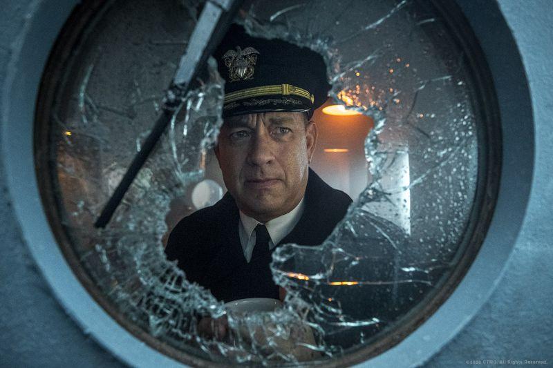 Cena do filme Greyhound. Nela vemos Tom Hanks, um homem branco e de meia-idade, com roupa de capitão. Ele olha por uma janela de navio quebrada.