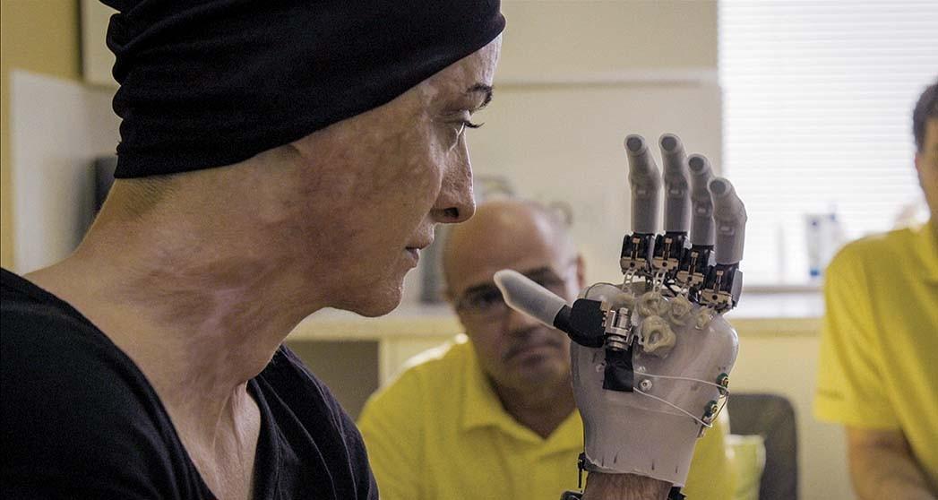Cena do documentário Colectiv, nela vemos a jovem Tedy, uma mulher branca, de toca preta e rosto com cicatrizes de queimadura, manejando uma prótese manual robótica cinza. Ao fundo, homens vestindo camisetas laranjas estão desfocados.