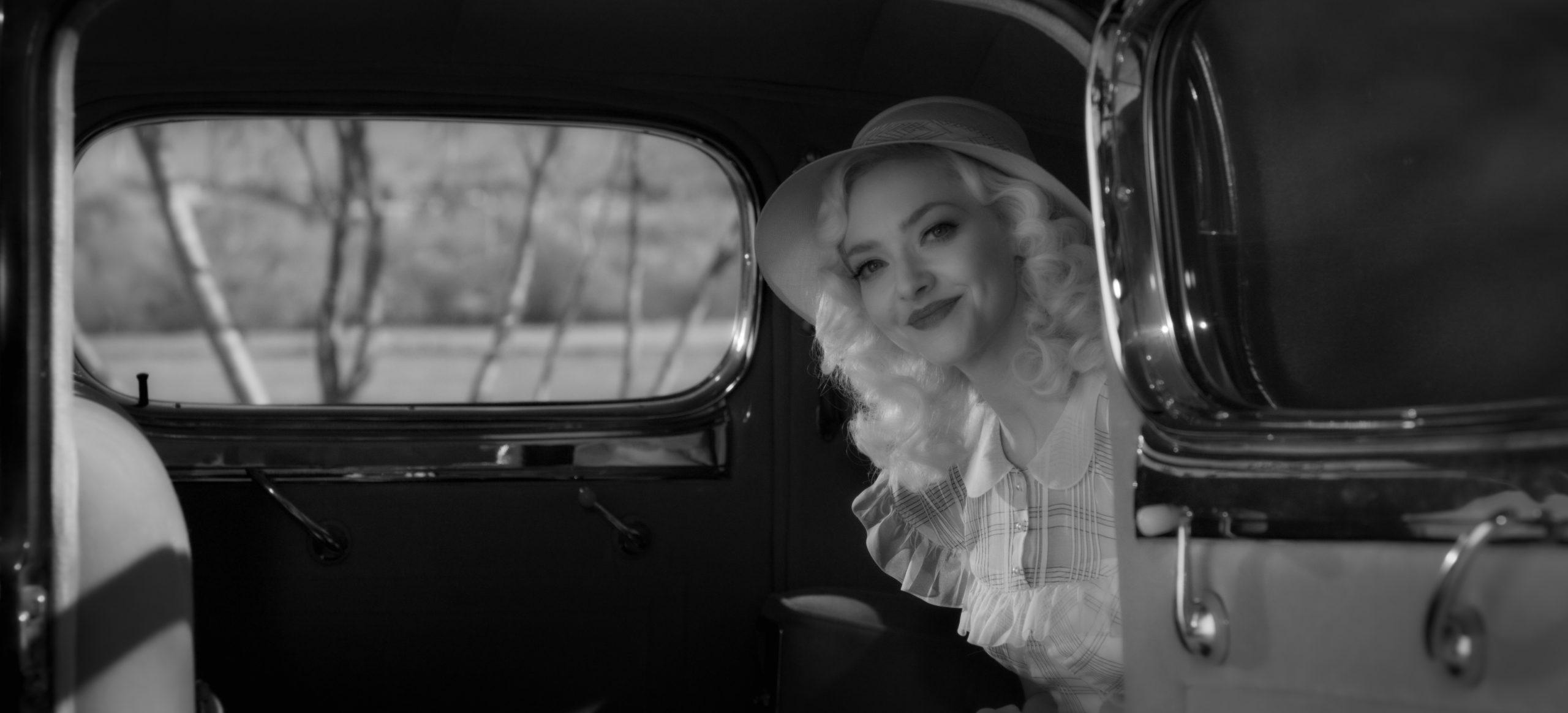 Cena do filme Mank. Vemos Amanda Seyfried, uma mulher branca, jovem e de cabelos loiros, olhando para fora de um carro antigo. Ela tem o cabelo curto, na altura dos ombros, e usa um chapéu branco. A imagem é em preto e branco.
