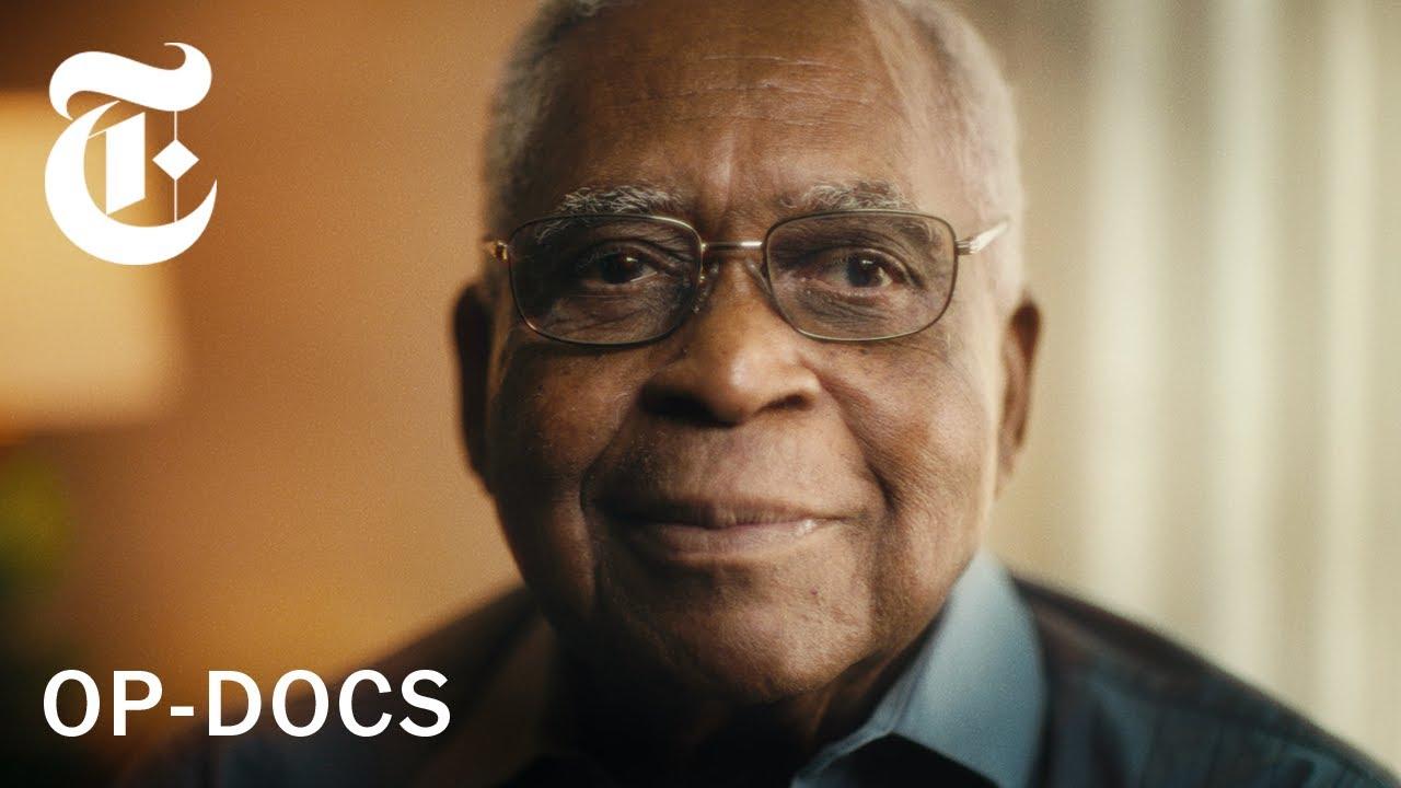 """Foto retangular. Nela temos o rosto de Horace Browns, um homem negro de 80 anos. Ele tem cabelos brancos e usa óculos quadrado. O fundo é desfocado. No canto superior esquerdo vemos o logo do The New York Times em branco. No canto inferior esquerdo lê-se em branco """"OP-DOCS""""."""