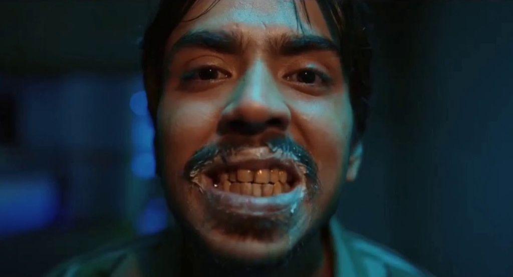 A imagem é uma cena do filme O Tigre Branco. Ao centro, vemos Adarsh Gourav, um homem indiano de bigode longo, barba rala, olhos pretos, sobrancelhas grossas e cabelo liso e comprido. Ele olha pra câmera como se estivesse olhando de frente para um espelho. Ela escova os dentes e abre um sorriso cheio de pasta na boca e no bigode. Ao fundo a imagem fica desfocada numa coloração azul escuro.