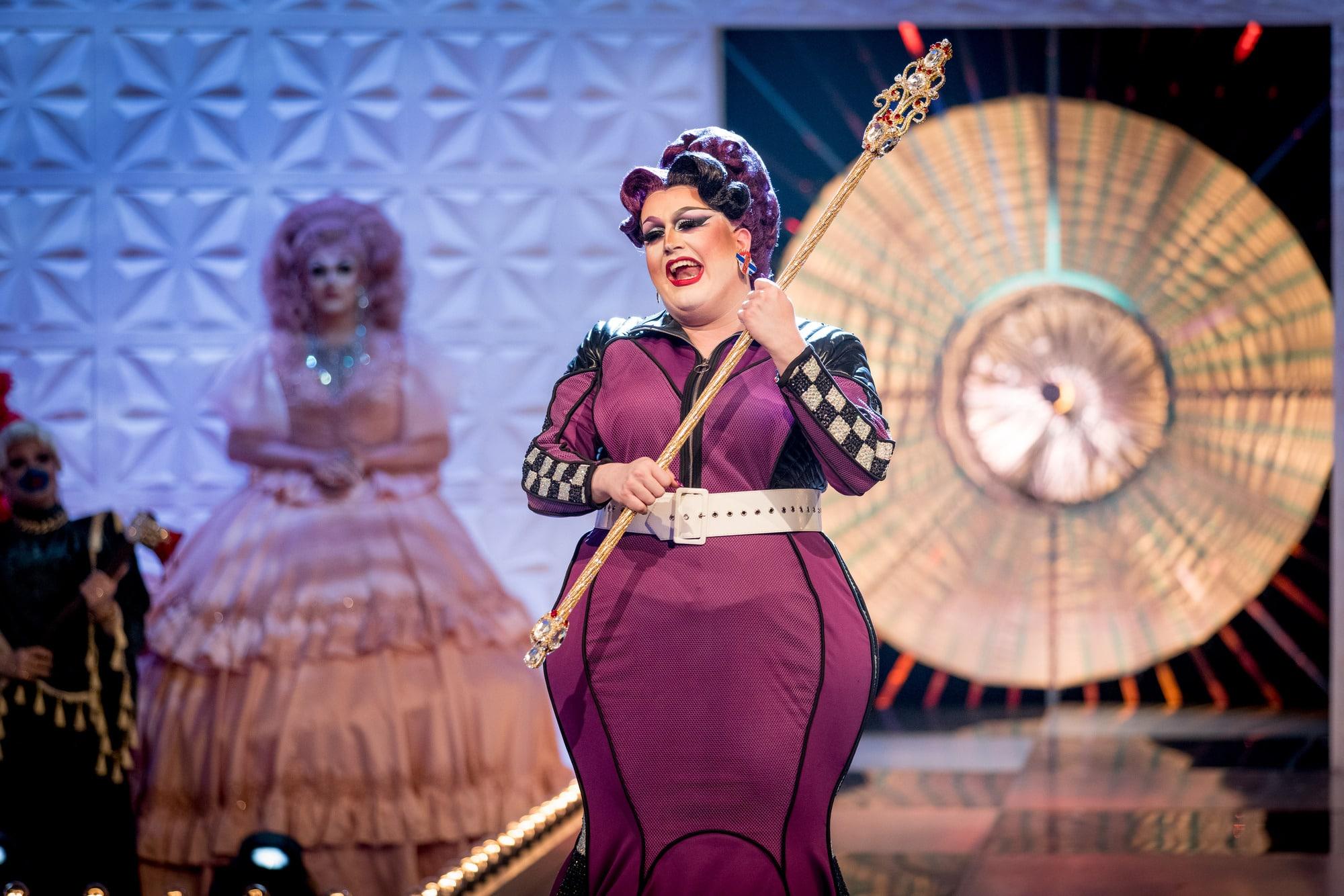 Cena de coroação da 2ª temporada de Drag Race UK. No centro da passarela, está Lawrence Chaney, sorrindo e empunhando seu cetro. Ela é uma drag queen escocesa, branca, gorda e que veste um vestido roxo. Seu cabelo é da mesma cor. Ao fundo, vemos vultos desfocados.