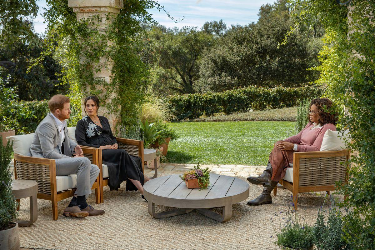 Imagem da entrevista de Oprah com o Príncipe Harry e sua esposa Meghan Markle. Na imagem, a apresentadora Oprah, uma mulher negra, de cabelos cacheados escuros e curtos, está sentada numa cadeira à direita. Oprah veste um conjunto de moletom rosa e uma bota marrom. À frente da apresentadora, está Meghan Markle, uma mulher negra de cabelos lisos castanhos presos num coque. Meghan usa um vestido longo preto, um sapato de bico fino também preto e maquiagem leve. Meghan olha para o lado esquerdo da imagem, onde está o príncipe Harry, um homem branco, de cabelos e barba ruivos. Harry usa u terno cinza claro e um sapato social marrom e olha para Oprah, à sua frente. O casal também está sentado e no meio do local existe uma mesa de centro cinza com um arranjo de flores coloridas. Todos são vistos de lado e estão em cima de um tapete bege e sob um pergolado, ao ar livre, cercados por árvores e plantas. Ao fundo, pode-se observar um gramado É de dia e está ensolarado.