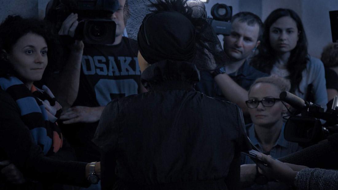 Cena do documentário Collective. A imagem mostra ao centro uma mulher de costas, vestindo um casaco preto e um chapéu da mesma cor decorado com penas. Ao redor dela, existem vários jornalistas, que estão de frente para a imagem, apontando microfones e câmeras em sua direção. A imagem é colorida em tons azulados e levemente iluminada, registrada no anoitecer.