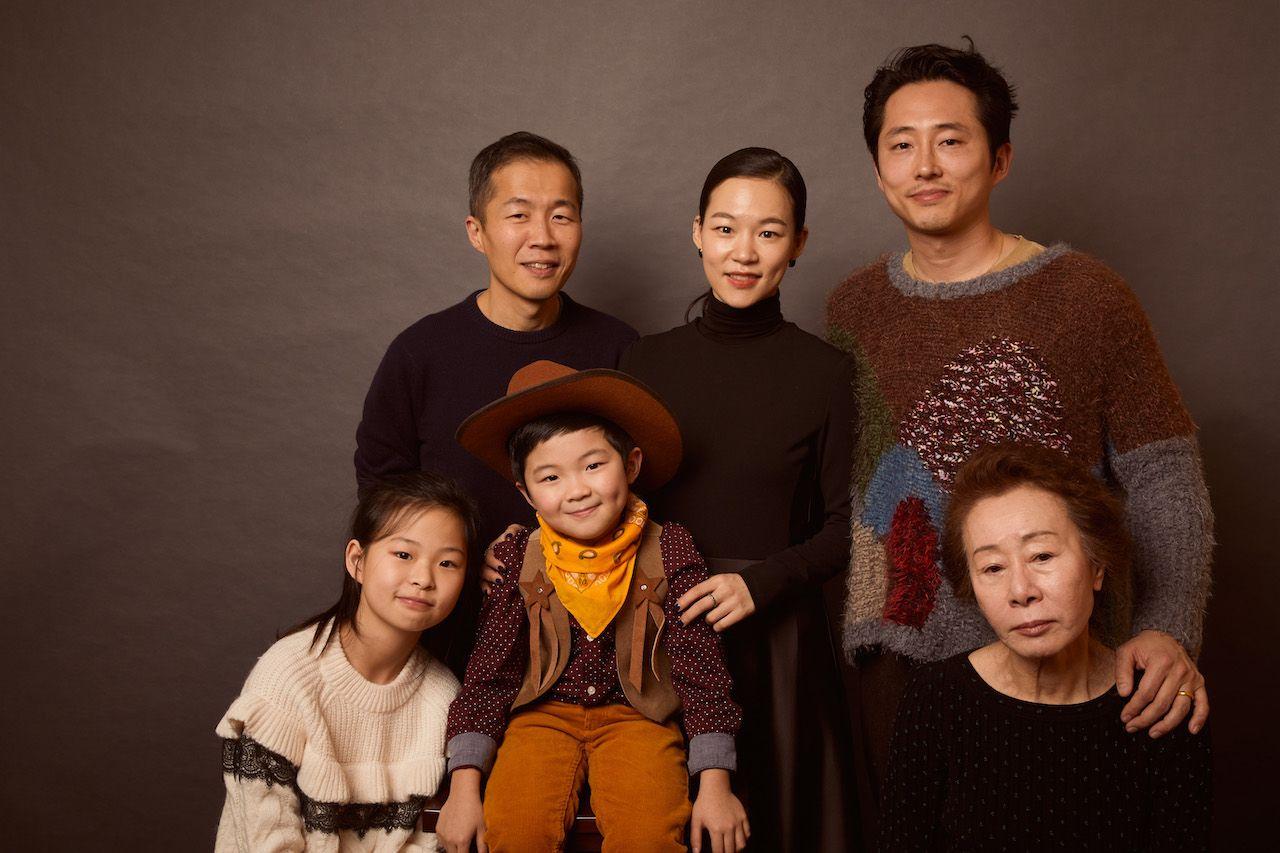 Imagem de divulgação do elenco e do diretor de Minari. Na imagem, Noel Cho, Alan Kim e Yuh-Jung Youn estão sentados à frente de Lee Isaac Chung, Ye-ri Han e Steven Yeun, que estão de pé na frente de um fundo cinza escuro amarronzado. Todos sorriem e posam para a foto.