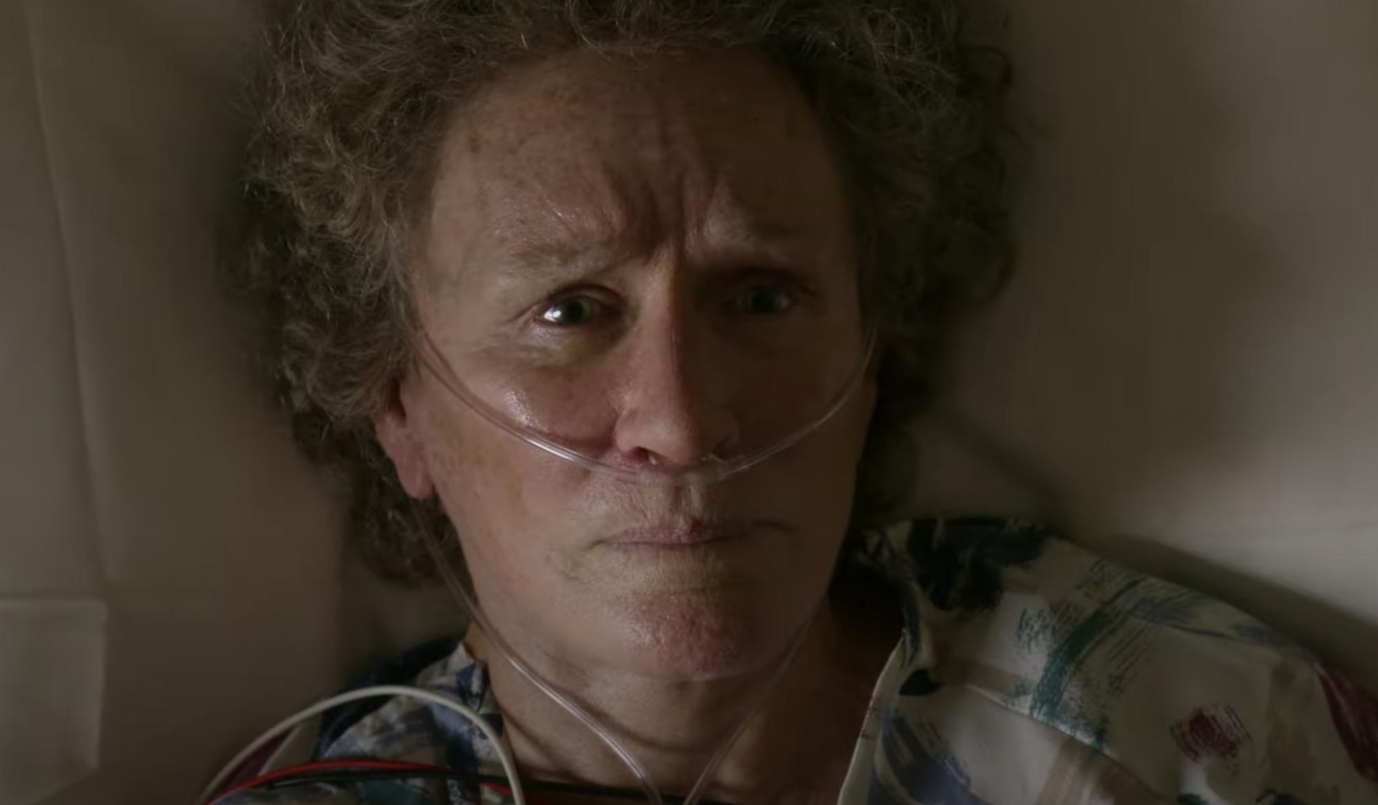 Cena do filme Era uma vez um sonho. Nela vemos um close no rosto de Glenn Close. A atriz, uma mulher branca e idosa, está deitada numa cama com tubos de oxigênio conectados ao nariz. Seus olhos são claros e seu cabelo é castanho. Ela tem nos olhos uma expressão de fraqueza.