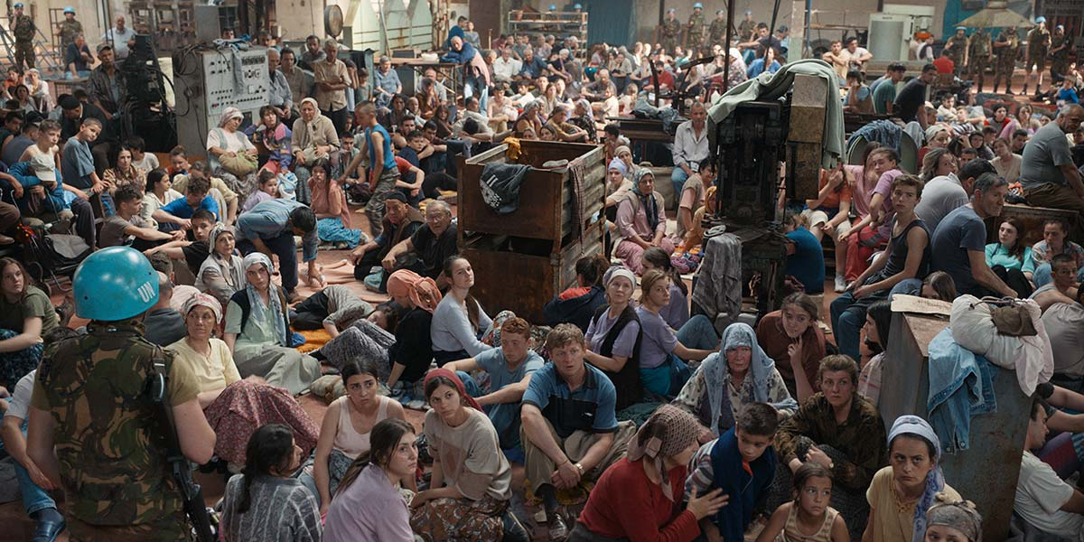 Cena de Quo Vadis, Aida?. Nela vemos dezenas de bósnios sentados no chão. Na frente a maioria são mulheres. Ao fundo, as pessoas da fotografia estão desfocadas.