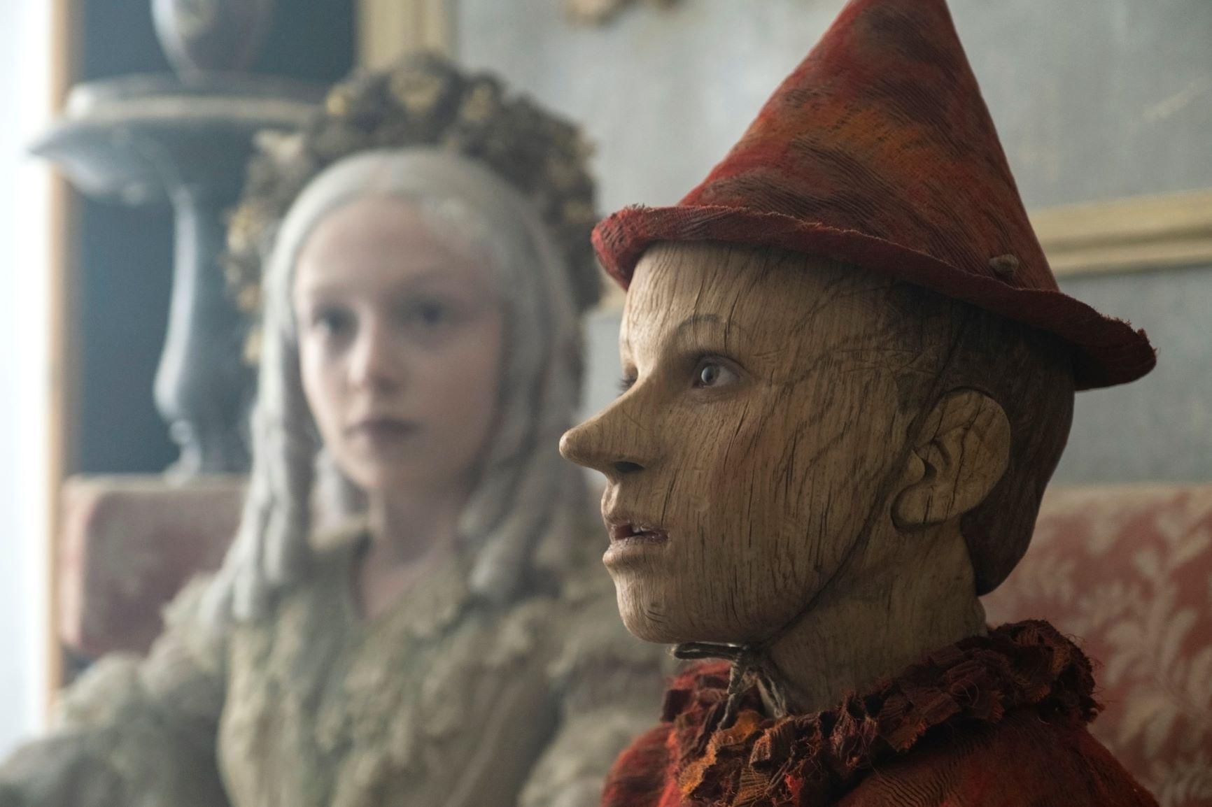Cena do filme Pinóquio. Nela vemos Pinóquio e a fada. Em primeiro plano, e focado, está Pinóquio, um menino feito de madeira, pele marrom, e nariz pontudo. Ele veste um chapéu em forma de cone vermelho, e uma blusa com gola da mesma cor. Desfocada, à esquerda, está a fada. Uma menina branca, de cabelos grisalhos azulados, e vestido verde.