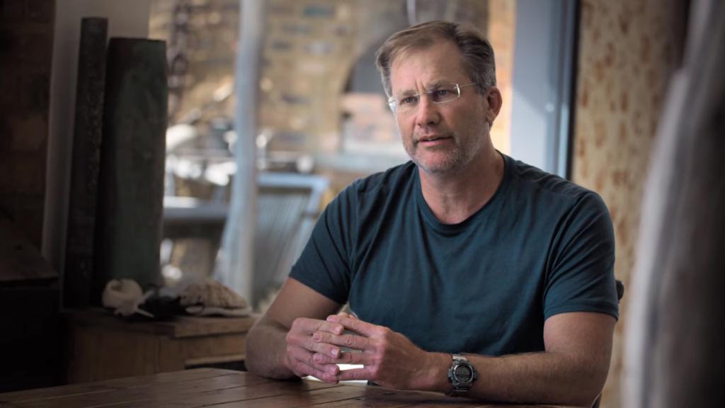 Cena do filme Professor Polvo. Nela, vemos Craig Foster sentado à mesa de sua casa, sendo entrevistado para as gravações do documentário. Ele é branco, de meia idade, usa óculos de grau com armação simples e transparente, e usa um relógio no pulso esquerdo. Ele veste uma camiseta verde marinho e tem as mãos juntas em cima da mesa.