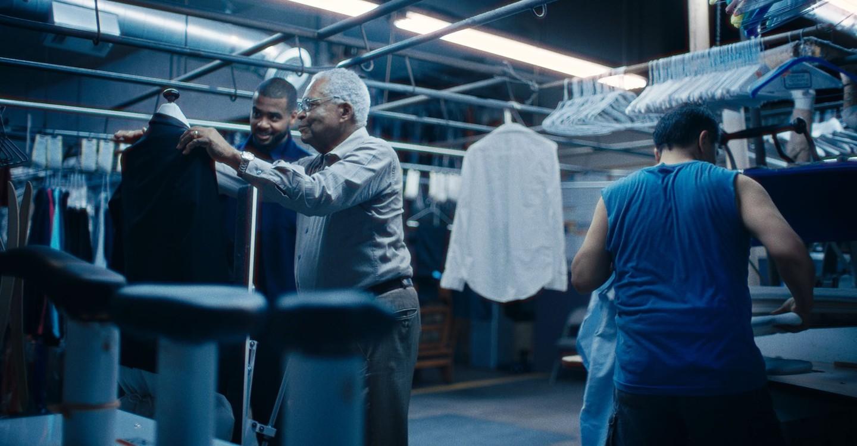 Foto retangular. À esquerda vemos Horace Bowers e Kris Bowers. Horace é um homem negro de 80 anos, ele veste calça e camisa social. Seu cabelo é branco. Kris é um homem adulto negro, seu cabelo é raspado e preto. Eles estão olhando para um terno preto. Atrás há  uma camisa branca pendurada no varal e vários cabides. O ambiente é uma lavanderia com efeito azul na foto.