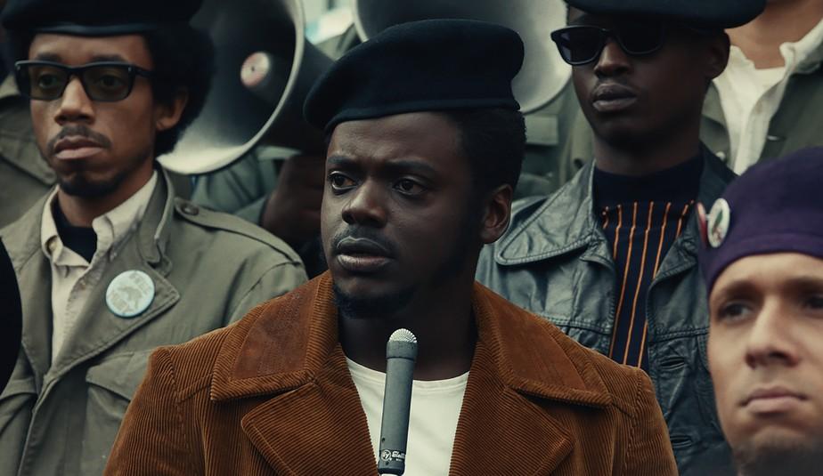 Cena do Filme Judas e o Messias Negro. Fred Hampton, interpretado por Daniel Kaluuya, veste uma boina preta, blusa branca com casaco marrom e na sua frente há um microfone. Atrás dele e ao seu lado estão homens de óculos escuros, boinas pretas, representando integrantes dos Panteras Negras.