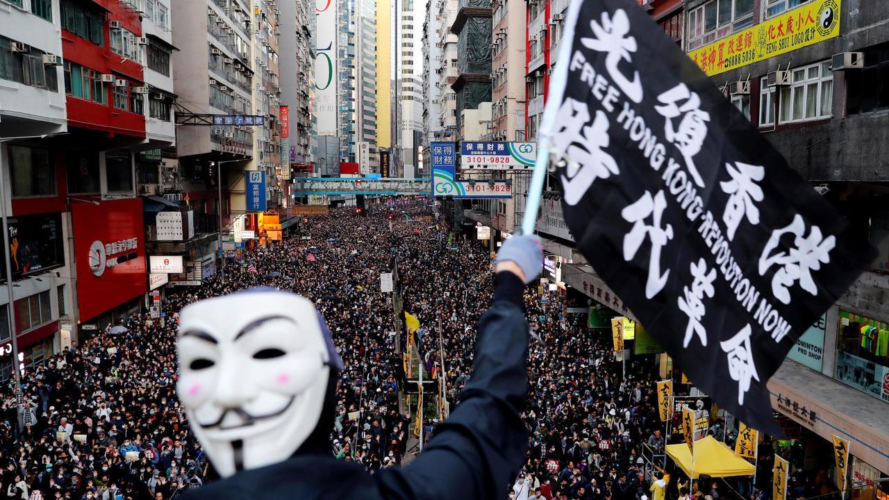 Fotografia de um protesto na cidade de Hong Kong. Em primeiro plano vemos um manifestante usando uma máscara do Guy Fawkes. Ele segura uma bandeira com os escritos FREE HONG KONG - REVOLUTION NOW. Ao fundo, podemos ver uma rua com milhares de manifestantes, preenchida de calçada a calçada. Aos lados, diversos prédios altos e fachadas de lojas.
