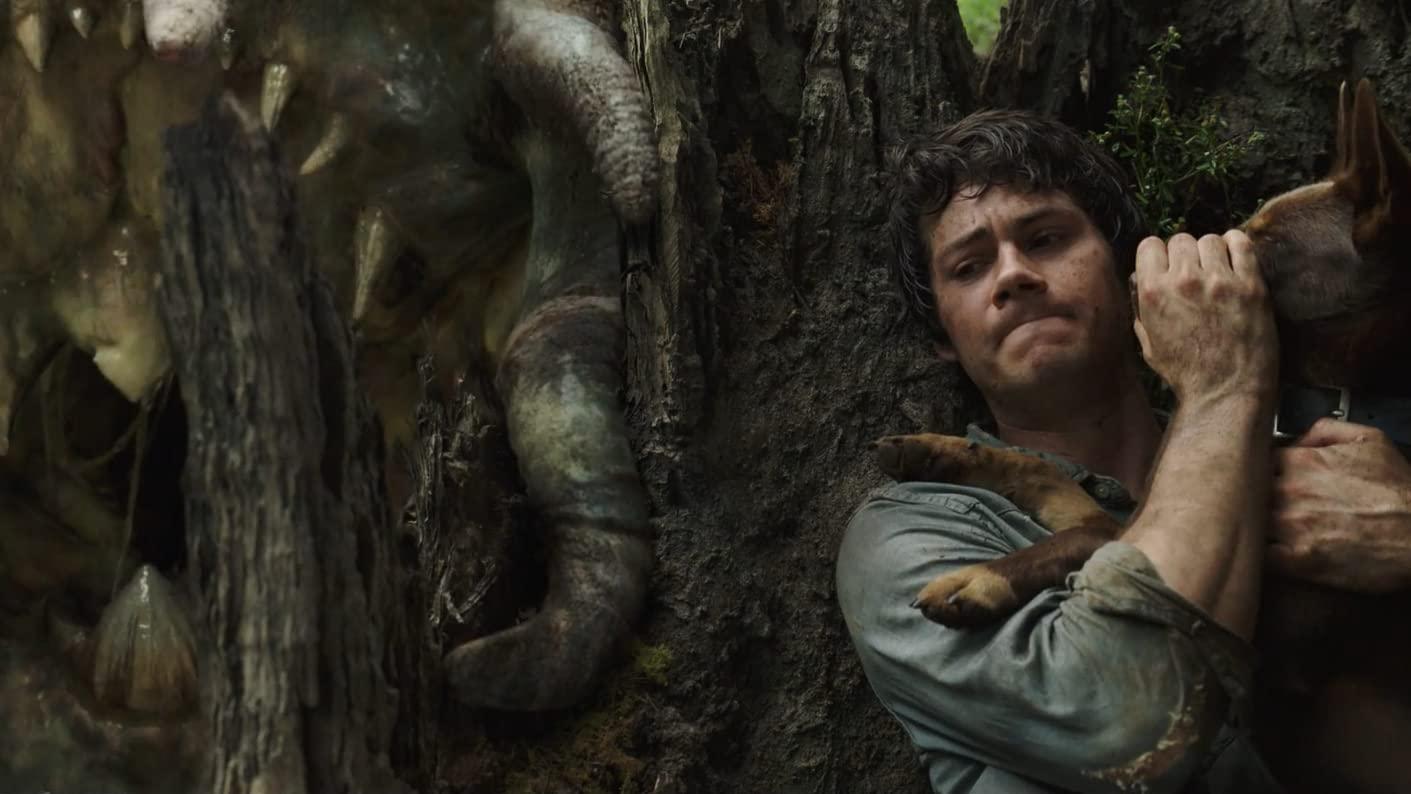 Cena do filme Amor e Monstros. Dylan O'Brien, um homem branco e jovem, está agachado atrás de um tronco de árvore. Ele está à direita da imagem, da altura do peito para cima. Ele usa uma camiseta suja azul clara de mangas compridas, e está com uma expressão de cautela, com os lábios comprimidos. Ele segura um cachorro de porte médio marrom, com a mão ao redor de seu focinho, prendendo. Na esquerda da imagem, há uma criatura meio gelatinosa com tentáculos e grandes presas tentando alcançá-los. Não há como identificar o tipo.
