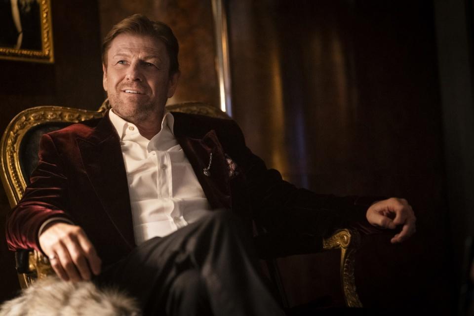 Cena da série Expresso do Amanhã. Nela está o personagem Sr. Wilford, vivido por Sean Bean, é um homem branco de cabelos loiros. Na cena, Wilford sorri enquanto está sentado em uma cadeira de veludo vermelho e bordas douradas num estilo clássico.