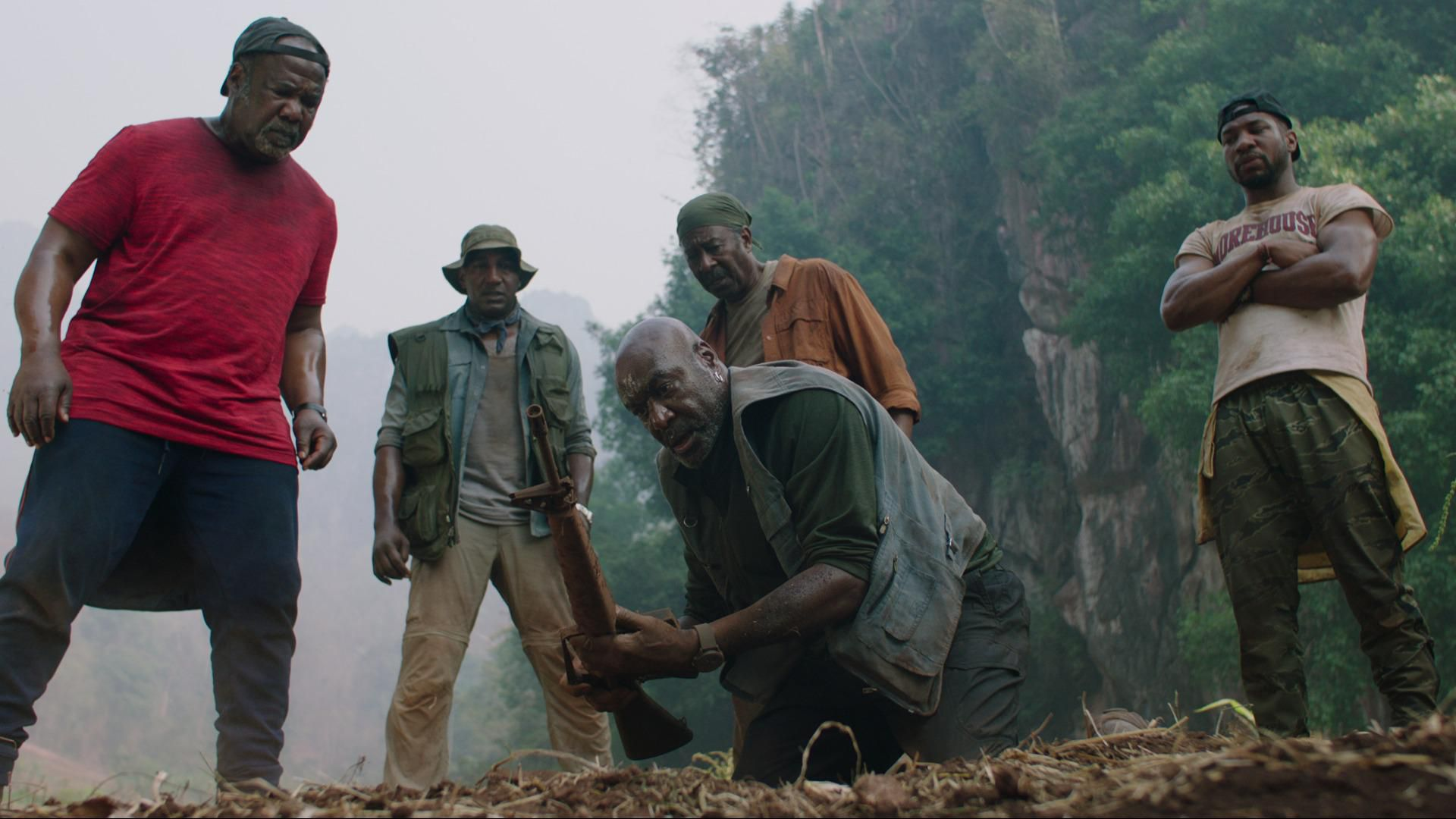 A imagem retangular é uma cena de Destacamento Blood. Da esquerda para direita vemos 5 homens. O primeiro é Isaiah Whitlock Jr, um homem negro de 66 anos. Ele está de pé e minimamente inclinado, enquanto usa um boné preto para trás, um relógio preto, uma camiseta limpa da cor vermelha e uma calça preta. À sua direita e um pouco mais atrás vemos Norm Lewis, um homem negro de 57 anos. Ele está de pé e usa um chapéu de caça verde, um relógio prateado, um colete verde por cima de uma jaqueta azul, que está por cima de uma camiseta cinza e uma calça bege. À sua direita e à frente, centralizado na imagem, vemos Delroy Lindo, um homem negro de 68 anos. Ele está agachado e segura um fuzil enferrujado nas mãos. Ele usa um colete azul sujo, por baixo uma camiseta de manga longa verde, um relógio bege e calças pretas. Atrás vemos Clarke Peters pela metade, um homem negro de 69 anos. Ele usa uma bandana verde, uma camiseta de manga longa laranja e aberta e por baixo uma camiseta verde. À sua direita vemos Jonathan Majors, um homem negro de 31 anos. Ele está na parte mais à direita da imagem e usa um boné preto para trás, uma camiseta bege com um bordão escrito em vermelho e calças verdes de exército. O plano de fundo é uma densa mata em uma montanha rochosa.