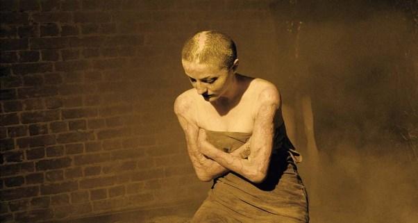 Cena do documentário Colectiv, nela vemos Tedy em um ensaio fotográfico artístico. Ela é branca, careca, tem a pele coberta de cicatrizes por conta das queimaduras e está ajoelhada na foto. Ela cruza os braços ao redor do corpo, cobrindo-se com um pano escuro. Ela está cheia de uma espécie de pó amarelo, quase como areia, para o ensaio fotográfico.