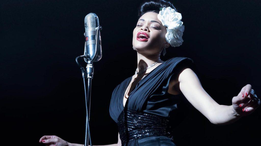 Cena do filme Estados Unidos Vs. Billie Holiday. Nela vemos Andra Day, uma mulher negra. Seus cabelos estão presos e há uma flor branca em sua cabeça. Ela veste um vestido preto e seus braços estão abertos. À sua frente há um microfone. O fundo da imagem é preto.