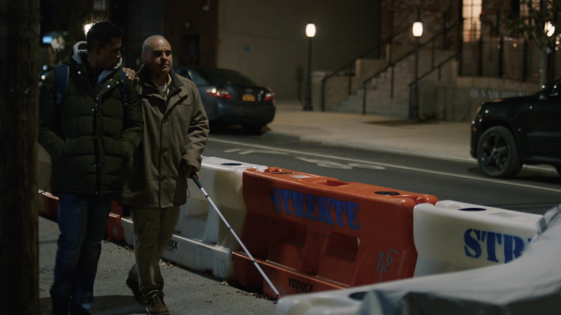 Cena do curta Feeling Through. Nela, vemos Terek e Artie andando de braços dados numa rua. Artie, um homem branco, careca, cego e surdo, segura Terek, jovem negro, no braço. Está de noite, Artie guia sua longa bengala branca. Ao lado deles, na rua, vemos objetos laranjas e brancos separando a rua da calçada.