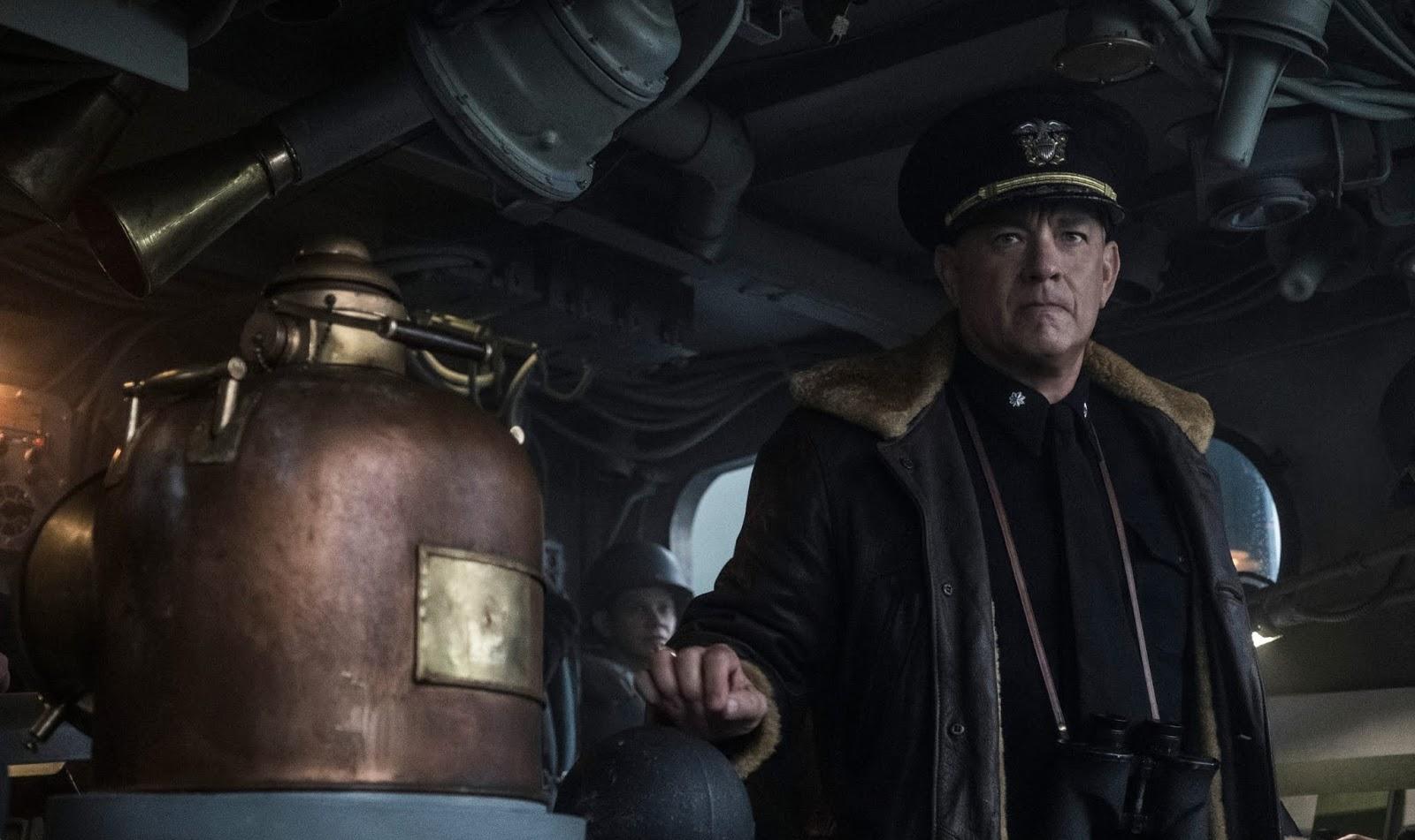 Cena do filme Greyhound. Nela vemos Tom Hanks, um homem branco e de meia-idade, com roupa de capitão. Ele está dentro de um barco, e veste uma jaqueta de couro escura e um cap preto com uma insígnia prateada, e um par de binóculos pendurado no pescoço.