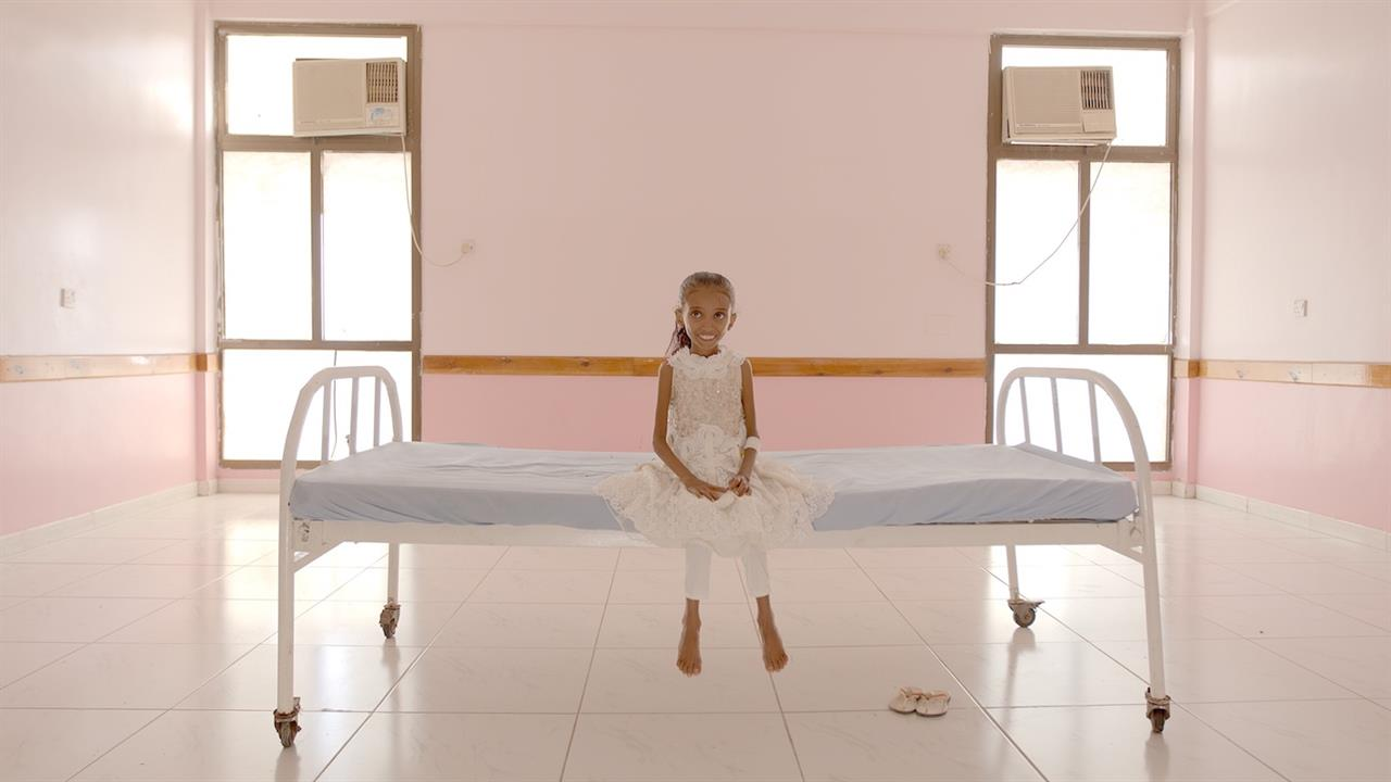 Foto de divulgação de Hunger Ward. Na imagem, uma menina iemenita, muito magra, aparentando ter cerca de cinco anos, de pele amarronzada e cabelos castanhos, senta sob uma cama, ao centro, e sorri para a câmera. Ela está em uma sala de paredes rosadas na clínica de reabilitação.