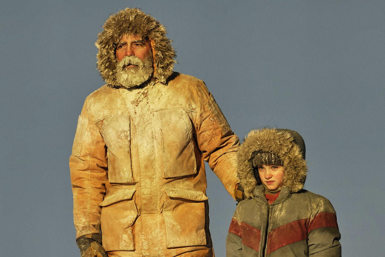 Cena do filme O Céu da Meia-Noite. Nela vemos George Clooney e uma criança. Eles estão vestindo casacos para neve e estão com neve em suas vestimentas. O céu ao fundo está limpo e o sol bate diretamente nas duas personagens, que olham para frente ao horizonte. George Clooney está com a barba congelada.