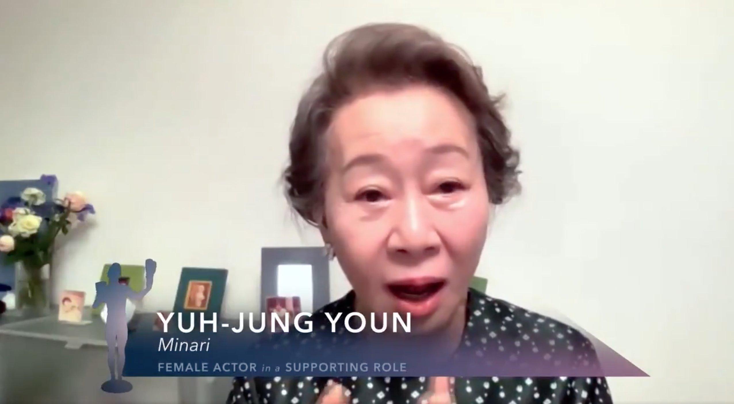 Yuh-Jung Youn está centralizada no centro da imagem, do peito para cima. Ela usa um casaco preto com bolinhas brancas e seus cabelos são curtos e castanhos. Ao fundo, vemos porta-retratos e arranjos de flores. Na parte inferior da imagem, lemos Yuh-Jung Youn, em seguida abaixo MINARI e depois FEMALE ACTOR IN A SUPPORTING ROLE em letras brancas com fundo azul.