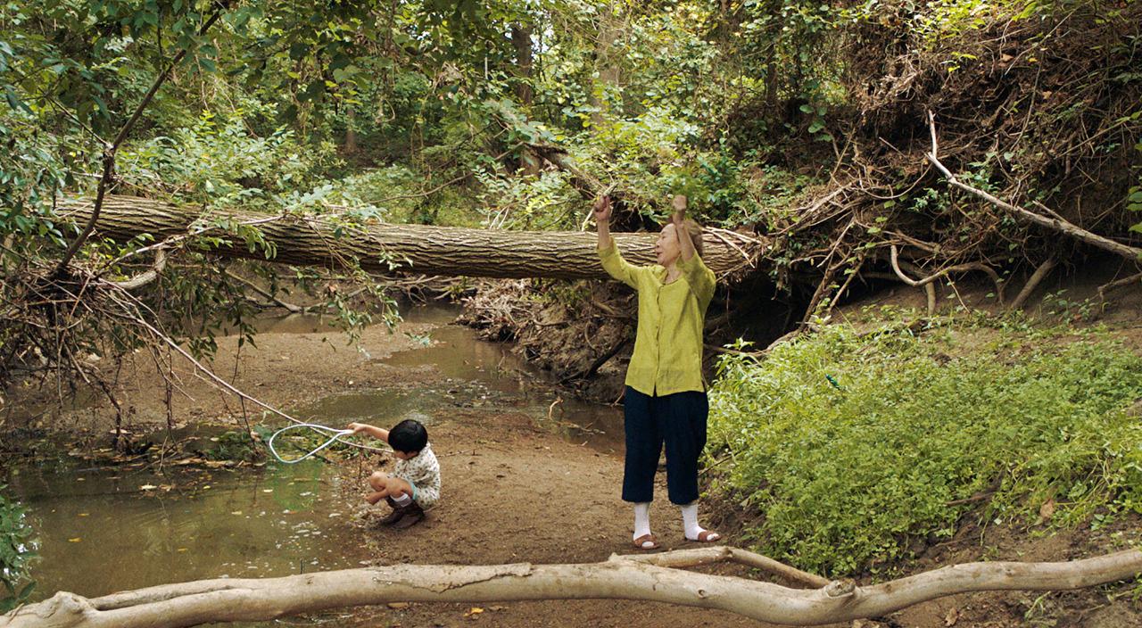 Cena do filme Minari. Nela vemos o neto e a avó na beira de um riacho. Ao lado direito da avó há uma plantação de minari, uma verdura popular na Coreia do Sul. O menino está sentado, de branco, e a avó está vestida de verde, segurando um galho acima da cabeça.