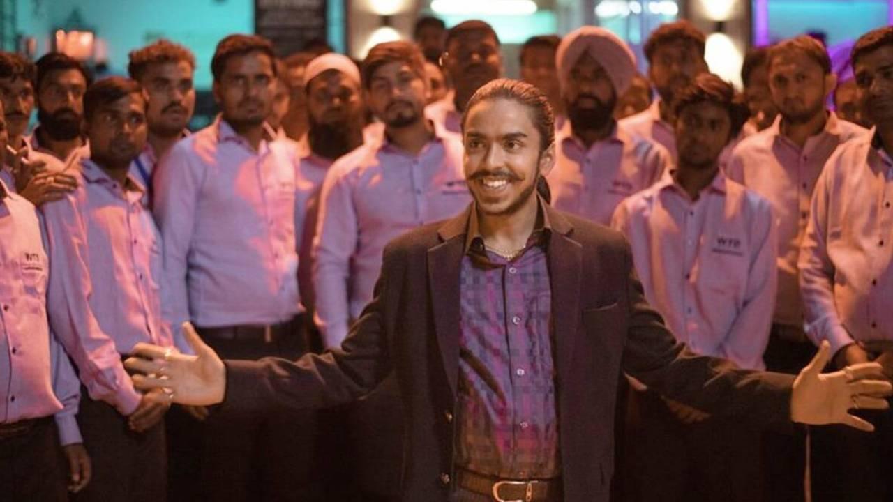 A imagem retangular é uma cena do filme O Tigre Branco. Ao centro e à frente vemos Adarsh Gourav, um homem de etnia indiana e pele parda. Ele tem um cabelo longo e preso em um rabo de cavalo, uma barba fina e um bigode longo. Ele sorri e possui os braços abertos. Ele usa um paletó preto aberto e por baixo uma camisa social xadrez em roxo e rosa. Ao fundo vemos 15 homens encarando a câmera, todos de etnia indiana e com camisas sociais brancas, porém aparentam ser rosas devido ao reflexo da luz.