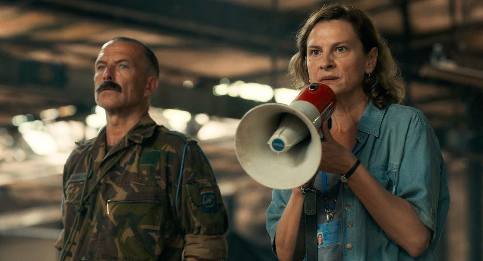 Cena de Quo Vadis, Aida?. À direita temos Aida, uma mulher branca, de olhos claros e cabelo castanho na altura do ombro. Ela veste camisa azul claro. Em suas mãos estão um megafone nas cores branco e vermelho. À esquerda temos um homem branco, com cabelo raspado e de bigode. Ele veste roupa militar.