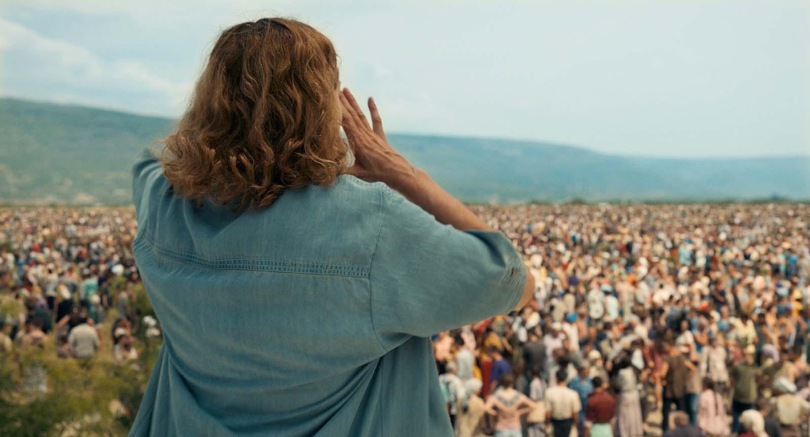 Cena de Quo Vadis, Aida?. Nela Vemos Aida de costas. Ela veste uma camisa azul. Suas mãos estão na altura da boca. Ela fala com centenas de pessoas que estão ao fundo da foto de forma desfocada.