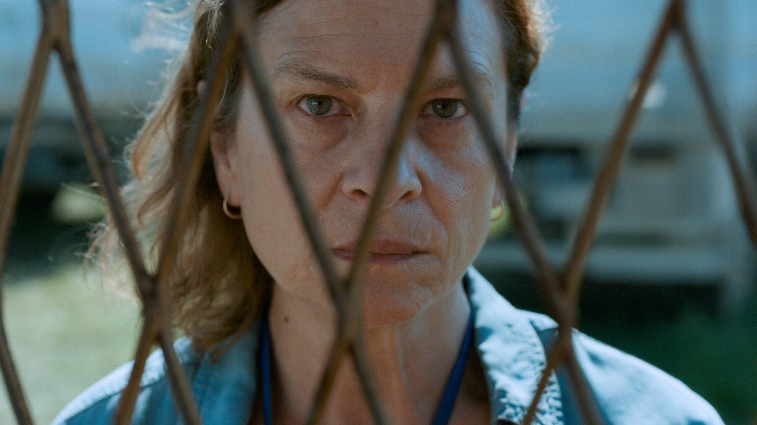 Cena do filme Quo Vadis, Aida?. Nela vemos a personagem principal atrás de uma grade, com um close no rosto. Ela é uma mulher branca e tem um olhar raivoso e preocupado.