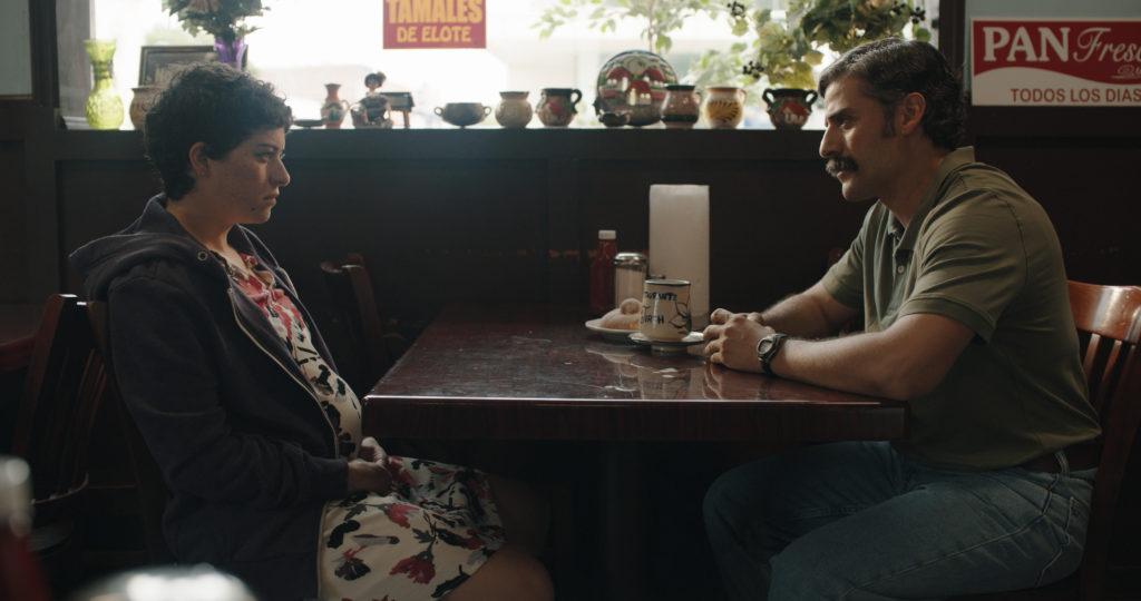 Cena do filme The Letter Room. Na foto constam duas pessoas, um homem e uma mulher, sentados de frente para outro num restaurante. O homem, vivido pelo ator Oscar Isaac, usa uma camisa pólo marrom por dentro da calça, calça jeans clara e um cinto. Ele possui pele morena, cabelos escuros e um bigode escuro, e está com as mãos cruzadas em cima da mesa. A mulher, vivida por Alia Shawkat, possui cabelos castanhos curtos, estilo pixie até nuca, e pele clara. Ela veste um vestido estampado floral e um casaco azul. O cenário é composto por uma mesa marrom, e atrás está uma janela com uma decoração feita de vasos numa prateleira.
