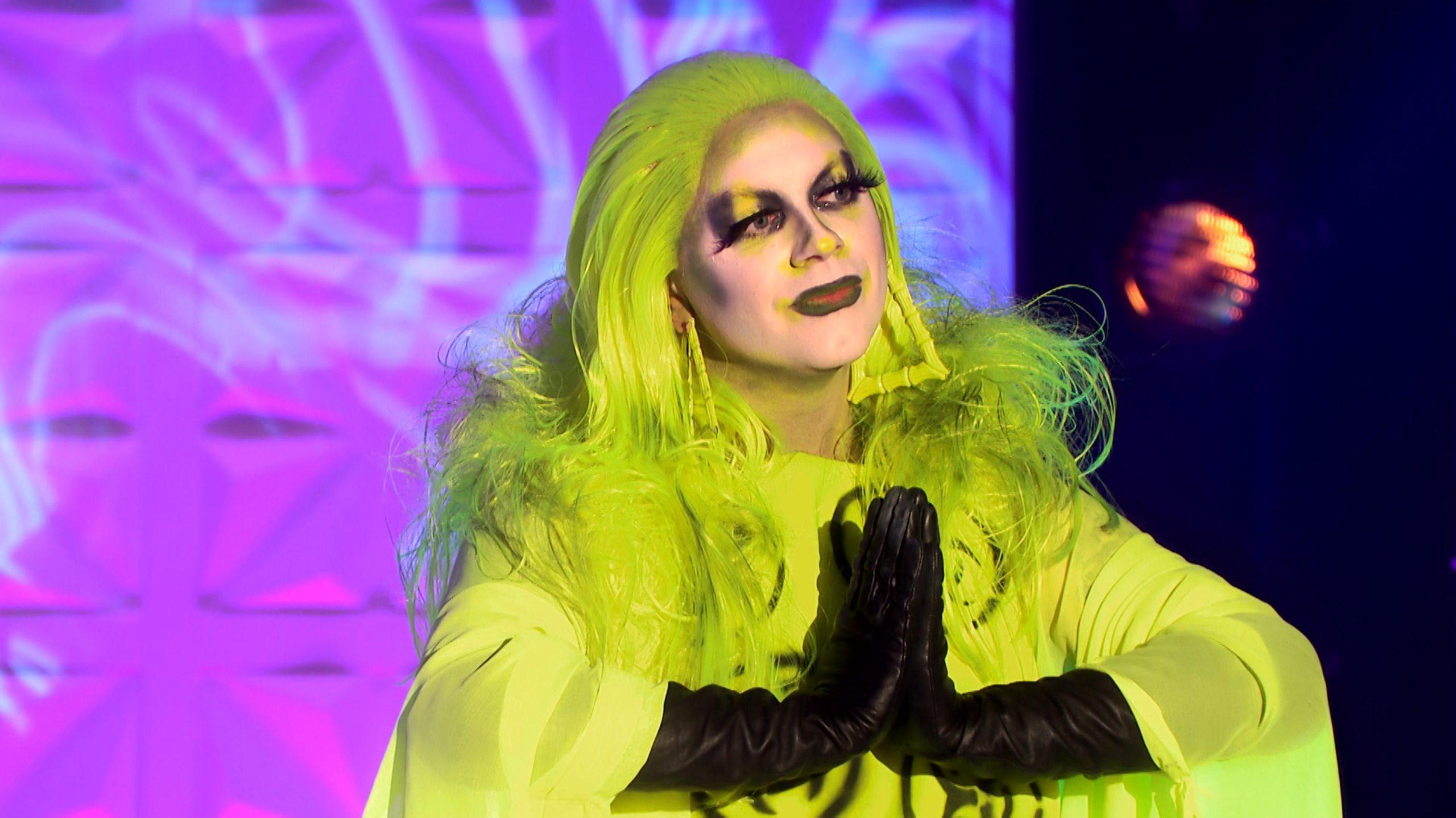 Foto de Ginny Lemon desistindo do programa. Ela está com o rosto pintado de branco, com tons de verde neon. Ela usa uma peruca verde abaixo dos ombros, e faz um sinal de mãos em prece com as luvas pretas. A roupa, um vestido com plumas verdes, é da mesma cor que detalhes da maquiagem nos olhos e no batom.