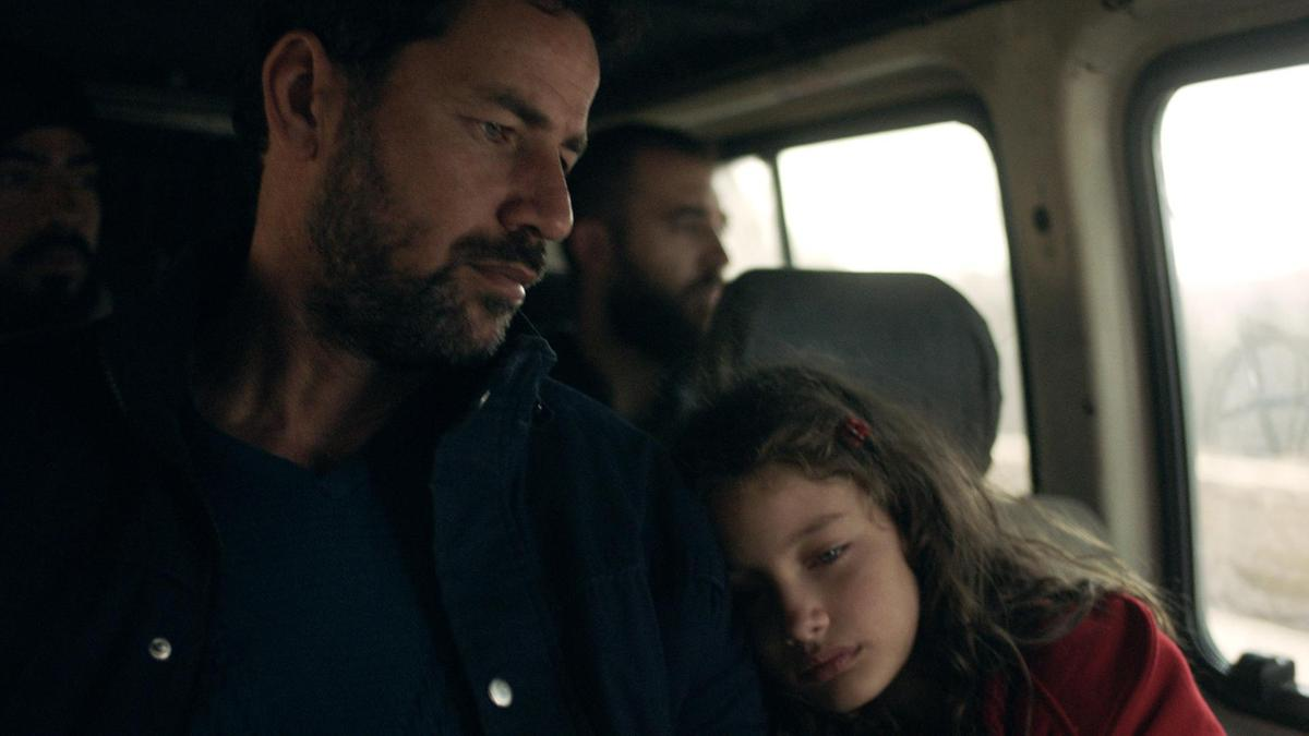 Cena do curta The Present. Nela vemos pai e filha sentados dentro de uma van. Ambos de pele clara, a filha usa um casaco vermelho e apoia a cabeça no braço do pai.
