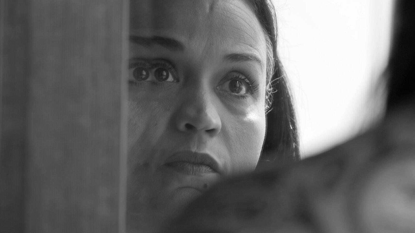 Cena do documentário Time. A imagem apresenta apenas o rosto de Fox Rich, principal personagem do filme, através de um espelho. Ela está se observando, com uma expressão alerta e séria. Ela é uma mulher negra, usa maquiagem no contorno dos olhos e seus cabelos estão alisados. No lado esquerdo da imagem, a moldura do espelho corta o reflexo de seu rosto. A imagem está em preto e branco.
