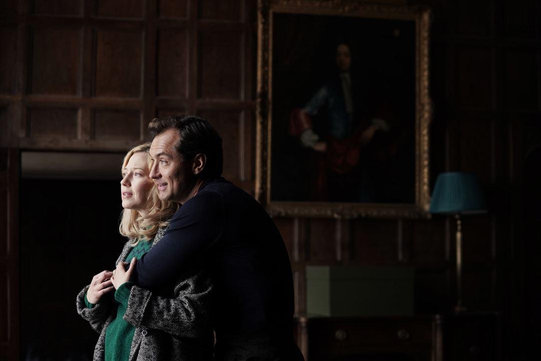 Cena do filme O Refúgio. Na imagem vemos a personagem Alisson O'Hara interpretada por Carrie Coon abraçada a Rory O'Hara, interpretado por Jude Law. Alisson é uma mulher branca e loira, vestindo uma blusa de lã verde escura, com um casaco acinzentado. Rory é um homem branco de meia idade vestido de uma camisa de manga longa de lã preta. O casal se encontra em uma sala escura com quadros ao fundo que só são notados pelos reflexos das molduras.