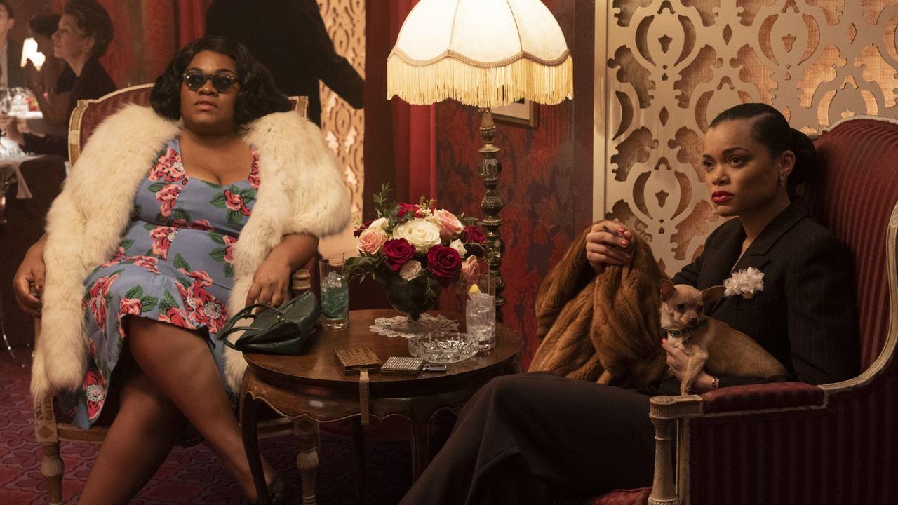 A imagem é uma cena do filme Estados Unidos Vs Billie Holiday. Nela, vemos as personagens Roslyn, interpretada por Da'Vine Joy Randolph, e Billie Holiday, interpretada por Andra Day, sentadas em duas poltronas, com uma mesa ao centro. Roslyn é uma mulher negra, de cabelos escuros e soltos, ela veste um vestido azul com flores rosas e um casaco de pelos brancos; Roslyn também está com óculos escuros e as pernas cruzadas. Billie é uma mulher negra, com cabelos escuros presos em um coque baixo, ela veste um terno e calça social preta e está com um casaco de pele marrom no braço direito, e um cachorro no braço esquerdo.