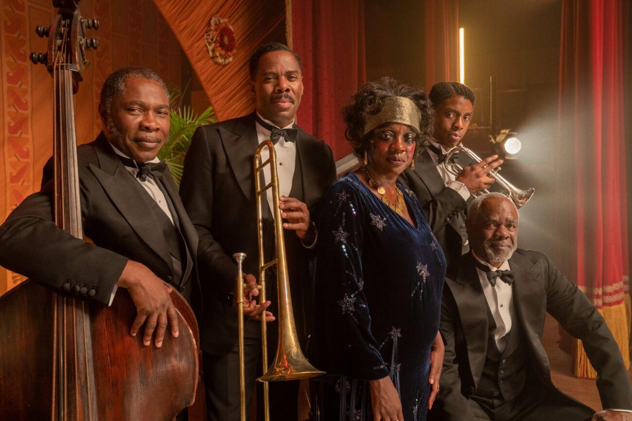Imagem promocional do filme A Voz Suprema dos Blues. A imagem mostra os atores do filme em cima de um palco. Há 4 homens e 1 mulher na imagem, todos são negros e os homens usam smoking preto. Da esquerda para a direita, Michael Potts está segurando um violoncelo, Colman Domingo segura um trombone, Viola Davis veste um vestido azul com detalhes brilhantes, Chadwick Boseman segura um trompete, Glynn Turman está sentado.