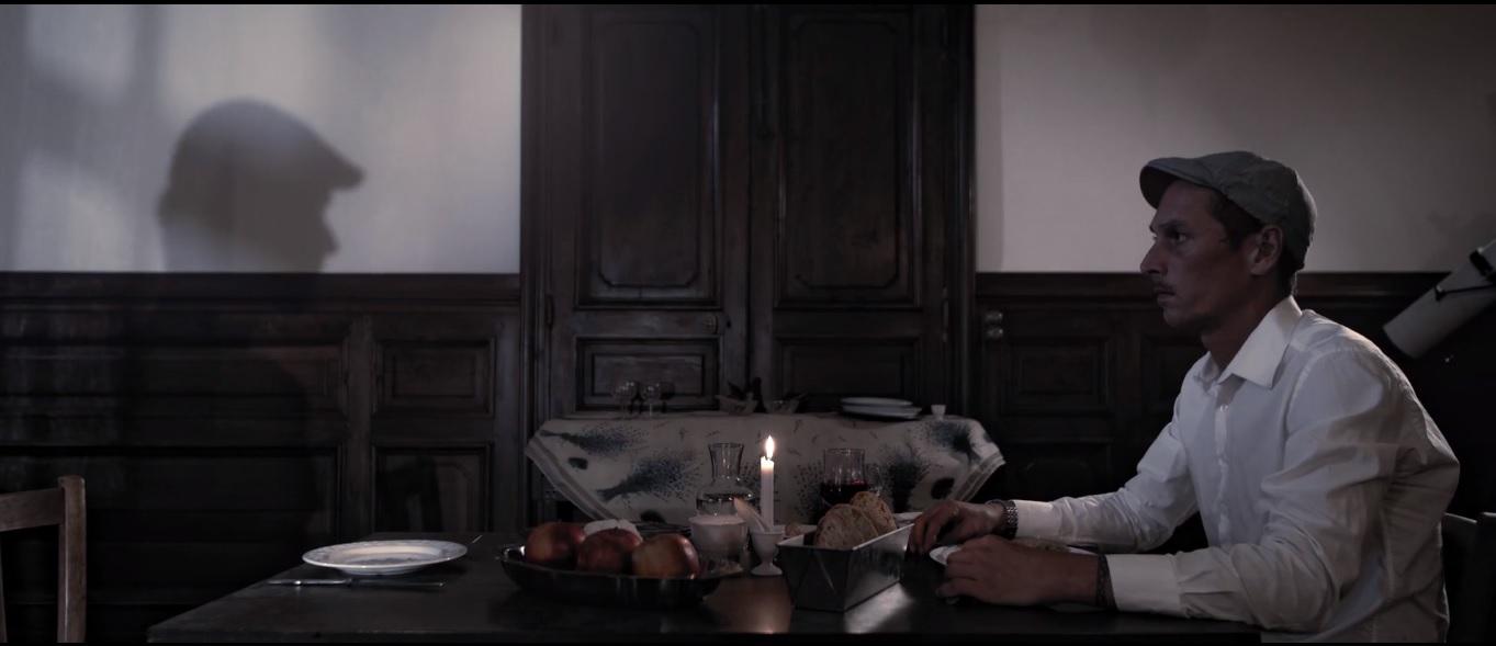 Cena do curta À L'ombre D'un Homme. Nele, vemos um homem jantando com a própria sombra. Ele usa boina bege e camisa branca, e está sentado ao lado direito da mesa de madeira, e sua sombra está do outro.