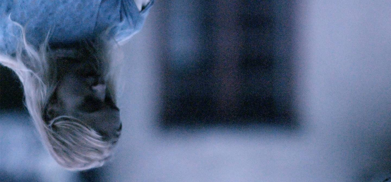 Cena do curta A Tale Best Forgotten. De cabeça-para-baixo, vemos uma mulher loira, olhando para baixo, ela usa roupa azul.