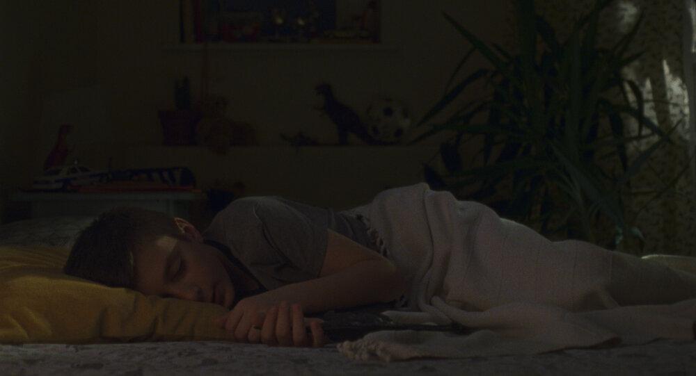 Cena do curta Acorde. Nela, vemos um garotinho dormindo de lado. Ele é branco, usa camisa cinza e deita num travesseiro amarelo, coberto por uma manta branca. Ao fundo, vemos uma parede amarela e uma planta.