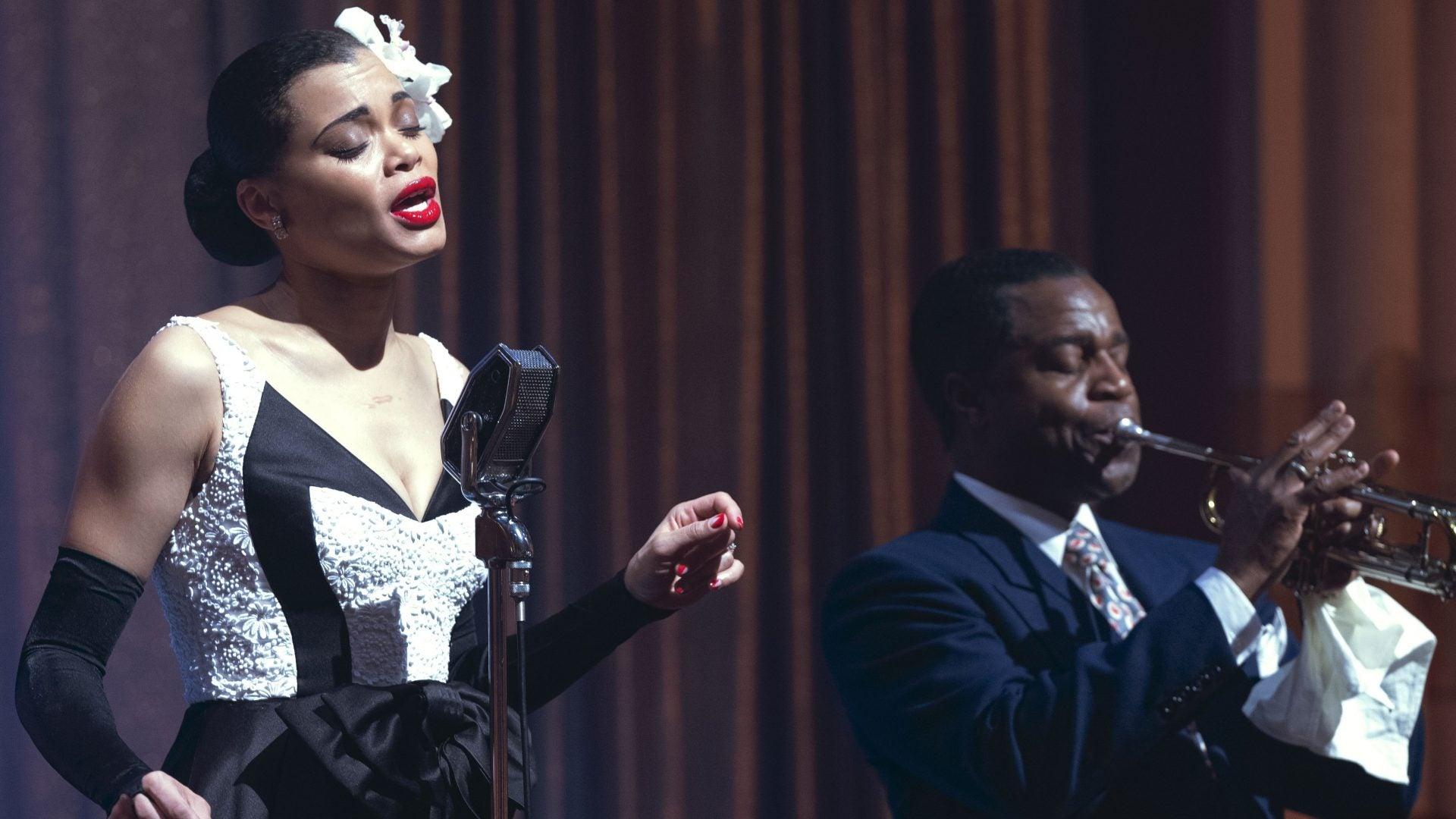 A imagem é uma cena do filme Estados Unidos Vs Billie Holiday. Na imagem, a personagem Billie, interpretada por Andra Day, está cantando no palco, à esquerda, e, à direita, vemos um músico com o que parece ser um trompete. Billie é uma mulher negra, com cabelos escuros e presos em um coque baixo e com uma flor presa no lado esquerdo da cabeça; ela usa um vestido branco e preto e está com luvas pretas nos braços.