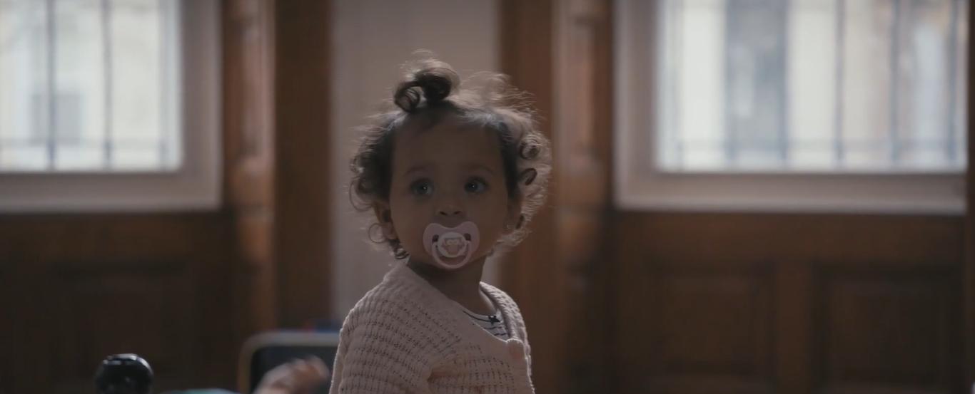 Cena do curta Nanny Cam. Vemos uma bebê com chupeta rosa e casaco rosa olhando para a esquerda. Ela tem cabelo curto e enrolado.