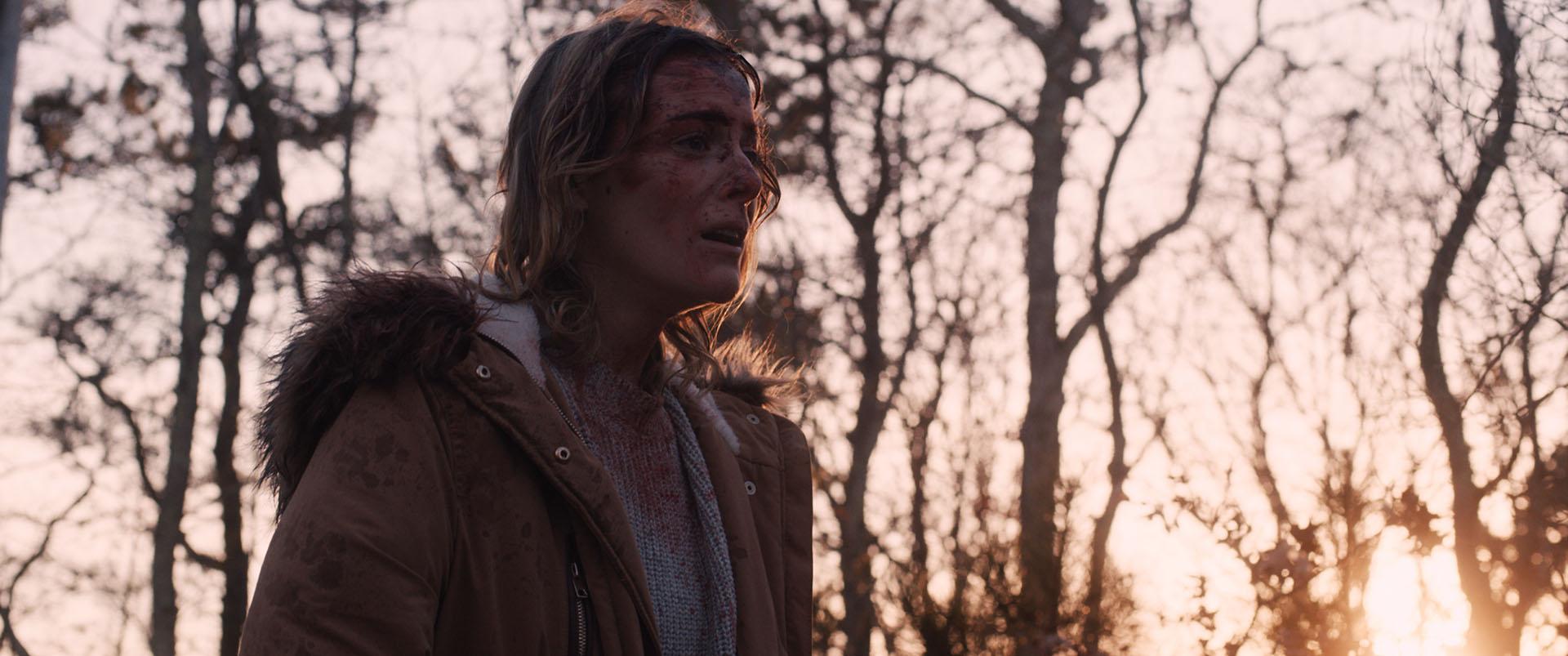 Cena do filme Corte Profundo. Nela, vemos uma mulher branca e loira na floresta, ela tem sangue sujando seu rosto e um semblante de cansaço. Está anoitecendo.
