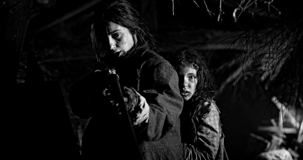 Cena do curta Dar-Dar. Em preto-e-branco, vemos uma mulher com uma arma, protegendo uma criança, agarrada às costas dela. Ao fundo, vemos folhas de árvores