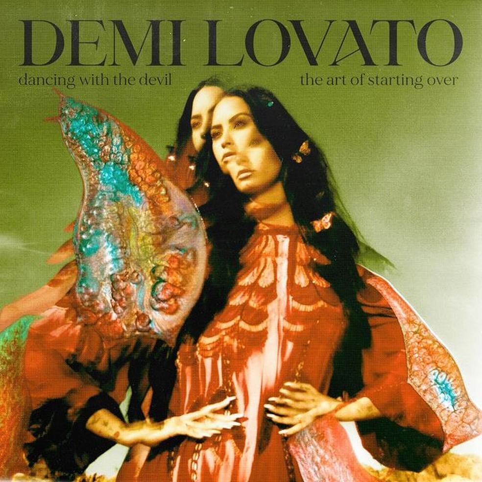 """Capa do álbum Dancing with the Devil… The Art of Starting Over de Demi Lovato. Na parte superior, está escrito """"Demi Lovato"""" em letras pretas e maiúsculas. Embaixo de """"Demi"""", está escrito """"dancing with the devil"""" em letras minúsculas e pretas. Embaixo de """"Vato"""", está escrito """"the art of starting over"""" em letras pretas e minúsculas. A cantora Demi Lovato está no centro da imagem, do quadril até a cabeça. Ela é branca e possui cabelos pretos compridos e lisos. Ela está olhando para o lado esquerdo. Ela usa um vestido vermelho com detalhes em branco no peito e tronco. Ela apoia as mãos na cintura e possui unhas compridas pintadas de branco."""