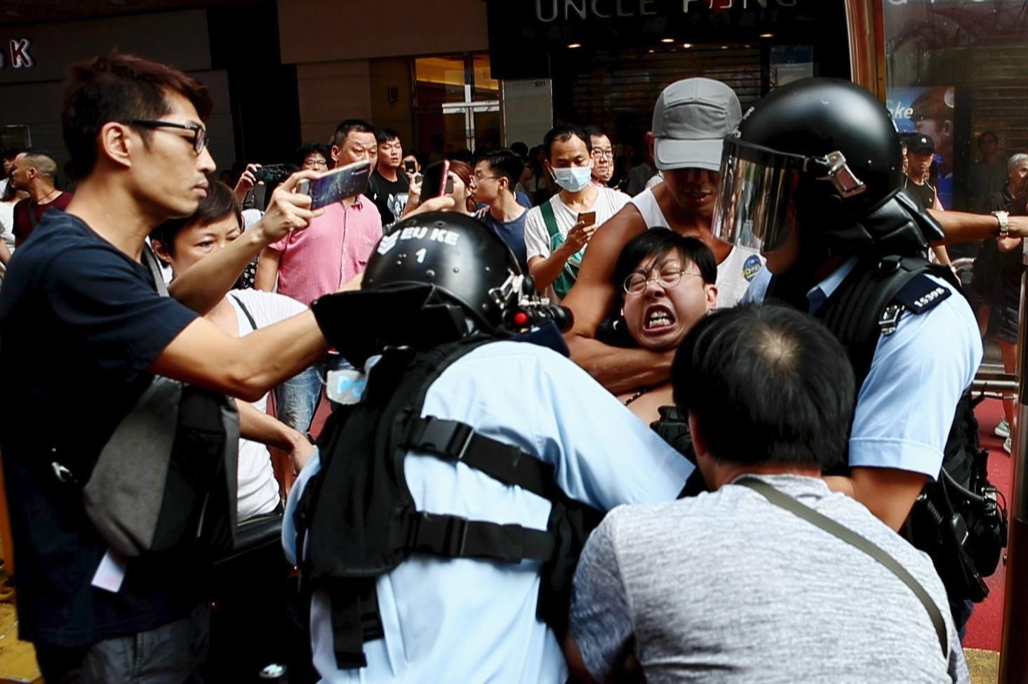 Cena do curta Do Not Split. Ao centro, vemos um grupo de policiais prendendo um manifestante honconguês. O manifestante está sendo segurado por um homem de boné com um mata leão. Pessoas em volta estão gravando a cena utilizando celulares.