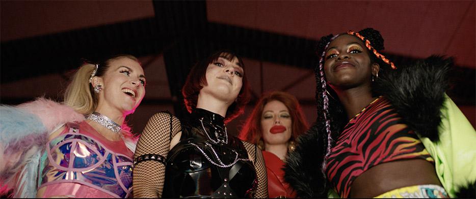 Cena do curta Dystopia. Vemos, de baixo para cima, 4 mulheres encarando a câmera, elas se vestem de forma colorida e extravagante.