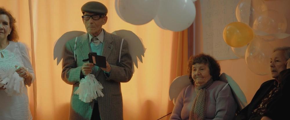 A foto mostra quatro pessoas idosas, três mulheres e um homem, estando as duas pessoas à esquerda em pé, e as duas à direita sentadas. Em destaque próximo ao centro está um senhor em pé, de óculos, usando uma boina e um terno cinza. Em suas mãos segura um smartphone, e em suas costas se penduram asas feitas de cartolina. A senhora sentada à sua esquerda também usa asas. Atrás das pessoas há uma cortina laranja e balões pendurados na parede, indicando um ambiente festivo.